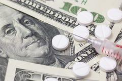 Шприц и пилюльки. Доллары США на заднем плане. Стоковая Фотография RF