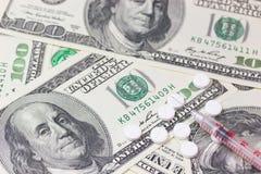 Шприц и пилюльки. Доллары США на заднем плане. Стоковые Изображения RF
