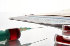 Шприц и пробирки с кровью на стеклянном столе и отчете Стоковое Изображение