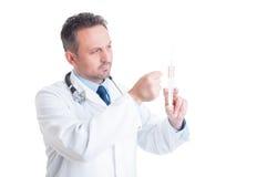 Шприц доктора или сотрудник военно-медицинской службы подготавливая и выстукивая стоковая фотография