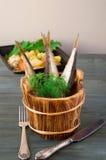Шпротины в деревянных бочонках с зелеными цветами на предпосылке картошек Стоковые Изображения RF