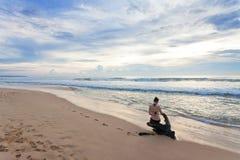 Шри-Ланка - Ahungalla - женщина сидя на пне на пляже стоковое фото