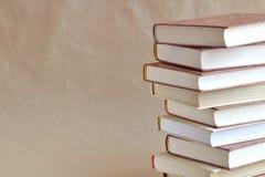 Штабелированные книги на бежевой предпосылке стоковое фото rf