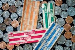 Штабелированные монетки США окруженные монетками и кренами бумаги Стоковое Фото