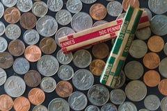 Штабелированные монетки США окруженные монетками и кренами бумаги Стоковые Фотографии RF