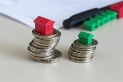 Штабелированные монетки с миниатюрным домом стоковые фотографии rf