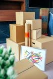 Штабелированные moving коробки и завод стоковые изображения