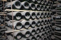 Штабелировано вверх по бутылкам вина в погребе стоковое фото