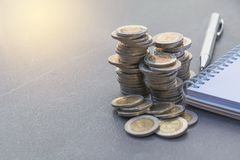 Штабелируйте монетку с ручкой и блокнот на таблице Финансовый, accountin стоковое изображение rf