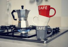 Штабелированные кофейная чашка и кофейник года сбора винограда на плите кухни Стоковые Изображения