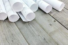 Штабелированные крены архитектурноакустических чертежей и планов дома на древесине Стоковые Изображения