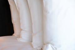 Штабелировать белых подушек на кровати Стоковая Фотография