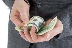 Штабелируйте банкноты 100 долларов в мужских руках Стоковое Изображение RF