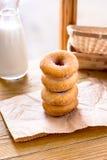 Штабелируйте donuts с бутылкой молока на деревянной предпосылке окном Стоковые Фото