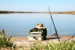Штанга и предметы первой необходимости удить на береге реки стоковое фото rf