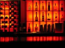 штанга освещенная контржурным светом предпосылкой разливает клуб по бутылкам Стоковые Изображения RF
