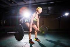 Штанга сильной женщины поднимаясь как часть режима тренировки crossfit Подходящая молодая женщина поднимая тяжелые весы на спортз стоковые фотографии rf