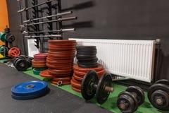 Штанги и гантели на поле в спортзале для разминки фитнеса прочности Стоковые Изображения RF