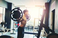 Штанги молодого человека фитнеса поднимаясь смотря сфокусированный разрабатывающ I Стоковое фото RF
