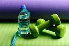Штанги около cyan измеряя крена и бутылки с водой ленты стоковая фотография rf