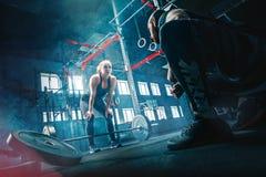 Штанги подходящей молодой женщины поднимаясь разрабатывая в спортзале стоковые изображения rf
