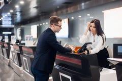 Штат в аэропорте проверяет в столе вручая билет к бизнесмену стоковые фотографии rf