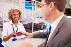 Штат на авиапорте проверяет внутри стол вручая билет к бизнесмену стоковое фото rf