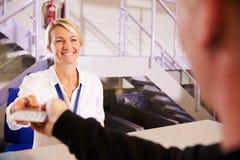 Штат на авиапорте проверяет внутри стол вручая билет к пассажиру стоковое изображение rf