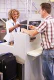 Штат на авиапорте проверяет внутри стол вручая билет к пассажиру стоковое фото