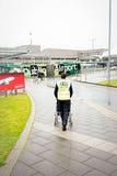 Штат члена авиапорта Дублина нажимая кресло-коляску для неработающего пассажира к зданию терминала на дождливый день лета, авиапо стоковая фотография rf