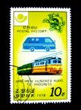 Штемпель напечатанный в Северной Корее показывает изображение голубых почтовых фургона и поезда на почтовая история 1874-1974 100 стоковое изображение rf