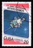 Штемпель почтового сбора Кубы от двадцатой годовщины вопроса программы Intercosmos показывает спутник космоса, около 1987 Стоковая Фотография