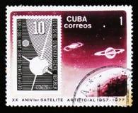 Штемпель почтового сбора Кубы показывает спутник в космосе, двадцатой годовщине лет научно-исследовательская работа по изучению к Стоковая Фотография