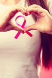 штемпель фондом находки дракой лечения рака молочной железы почтовый Женские руки делают сердце на розовой ленте Стоковое фото RF