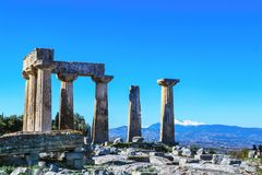 Штендеры от виска Аполлона в старых руинах Коринфа Греции с snowtopped горами на заднем плане стоковая фотография rf