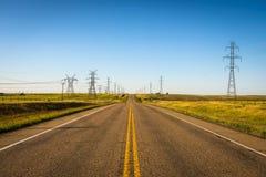 Штендеры электричества вдоль пустой дороги в Альберте, Канаде стоковая фотография