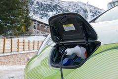 Штепсельная вилка электрического автомобиля поручая в городке горы зимы Стоковая Фотография