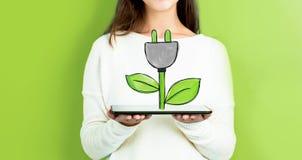 Штепсельная вилка Eco при женщина держа таблетку стоковое фото