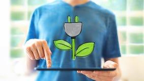 Штепсельная вилка Eco с человеком используя планшет стоковая фотография rf