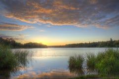 штилевое цветастое озеро над заходом солнца живой Стоковая Фотография