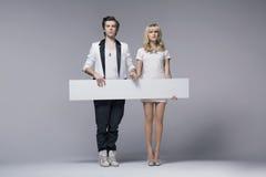 Штилевые молодые пары держа пустую доску Стоковое Фото
