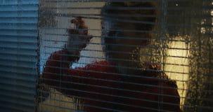 Шторм мальчика наблюдая через окно акции видеоматериалы