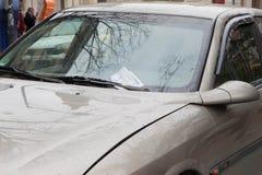 Штраф за нарушение правил стоянки помещенный под лезвием счищателя на windscreen незаконно припаркованного автомобиля Стоковое фото RF