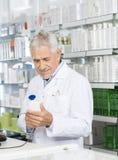 Штрихкод скеннирования аптекаря бутылки шампуня на счетчике Стоковые Изображения