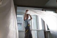 Штукатур восстанавливая крытые стены и потолки Заканчивая работы Стоковая Фотография