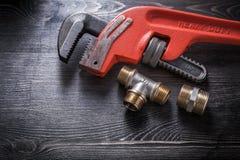Штуцеры трубопровода универсального гаечного ключа на деревянной доске Стоковое Фото