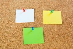 Штыри и notepaper канцелярской кнопки на pinboard Стоковые Изображения