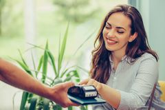 Штырь безопасностью женщины входя в читателе кредитной карточки с положением официанта на кофейне стоковые фото
