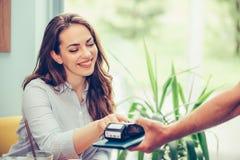 Штырь безопасностью молодой женщины входя в читателе кредитной карточки пока оплачивающ кредиткой на кафе стоковые изображения