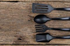 Шумовка черной пластичной кухни установленная, лопата сковороды на деревянном Стоковое фото RF